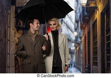 Elegant couple with umbrella walking outdoors in the rain