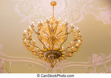 elegant crystal chandelier. vintage pendant chandelier. Large crystal chandelier with pendants in ceiling. Luxurious round lamp in their glass bowls in the great hall. Intererniy light indoor.