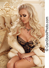 Elegant cute blond woman in fur coat with long curly hair style, sitting on royal sofa in luxury modern interior. Beauty glamour fashion style photo portrait.
