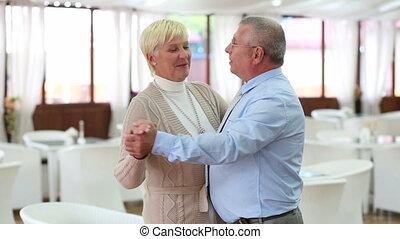 Elegant dance - Elegant senior couple dancing in a caf