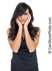 Elegant dark haired model posing touching her cheeks on...