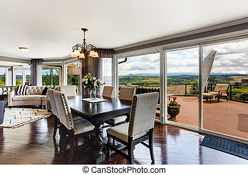 Elegant dining area with walkout deck in luxury house