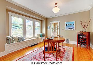 Elegant dining room with window bench with cherry hardwood floor.