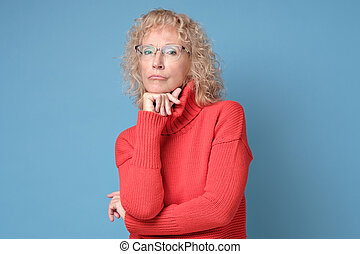 elegant elderly lady in red sweater wearing glasses looking at the camera