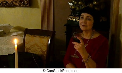 Elegant elderly woman lonely sitting with a cup of wine.
