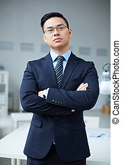 Elegant employer - Serious businessman in suit standing in...