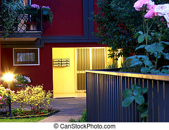 elegant entry of a luxury home at night with lamp and roses