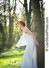 Elegant fashion bride in white dress standing outdoors