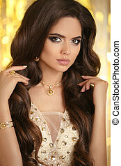 Elegant fashion brunette woman portrait in gold. Wavy hair style. Matte lips Makeup. Healthy shiny hairstyle. Sexy girl model with golden jewelry over bokeh lights background.