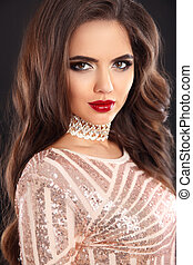 Elegant fashion brunette woman portrait. Wavy hair style. Red lips Makeup. Healthy shiny hairstyle. Sexy girl model in sequin dress isolated on black background.