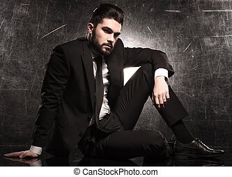 elegant fashion model in suit and tie resting