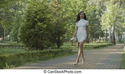 Slim elegant gorgeous african american female in stylish classic stiletto shoes and white mini dress holding handbag, stepping along sidewalk in summer park. expressing confidence and beauty.