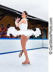Elegant figure ice skater on ice rink