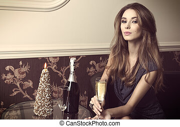 elegant girl with champagne - indoor portrait of sexy woman...