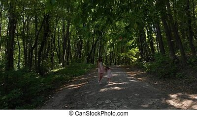 Elegant girl with her young daughter walking and having fun in the woods between the trees.
