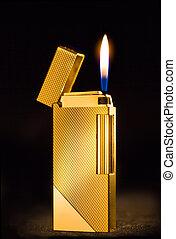 Elegant golden gas lighter against a dark background