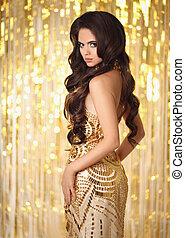 Elegant gorgeous brunette in gold evening dress. Fashion...