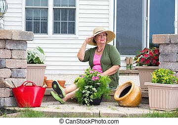 Elegant Grandma posing as she pots up plants