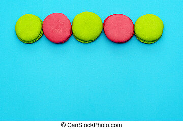 elegant green and pink macaroons are laid in one line on top of a blue background. copy space