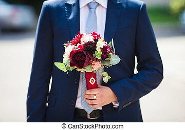 Elegant handsome groom in blue suit with wedding bouquet