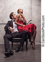 Elegant handsome man kissing his girlfriend in a shoulder. Girl sitting on his knees