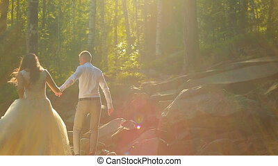 Elegant happy wedding couple kissing in the forest on sunset