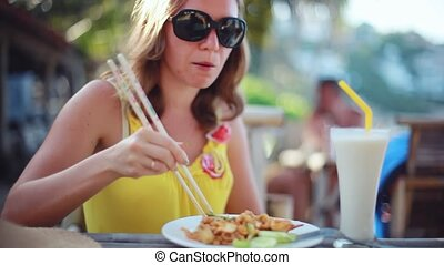 Elegant happy woman wearing sunglasses eating pad Thai...
