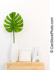 Elegant home decor with picture frame and tropical leaf