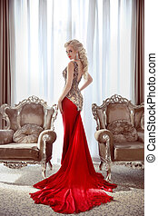 Elegant lady. Beautiful blond woman model in fashion dress with long red train posing between two modern armchairs in front of window at interior.