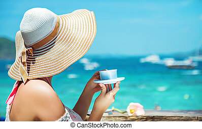 Elegant lady drinking coffee on a beach