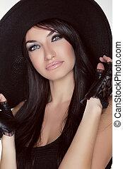 Elegant lady. Fashion brunette woman model posing in black hat isolated on white background. Vogue style