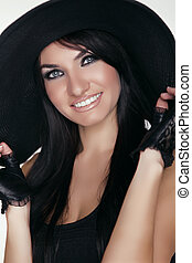 Elegant lady. Happy smiling brunette woman model posing in black hat isolated on white background. Vogue style