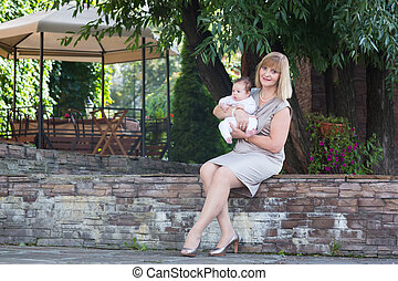 Elegant lady in a formal dress holding a baby in the garden