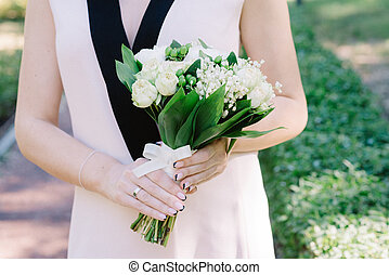 Elegant lily of the valley wedding bouquet in hands of the bride