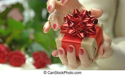 Elegant little gift box in female hands. Close up senior...