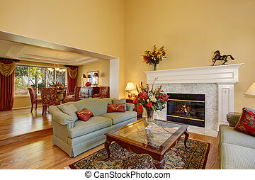 Elegant living room interior with white fireplace and flowers.