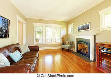 Elegant living room with fireplace and leather sofa with beige walls.