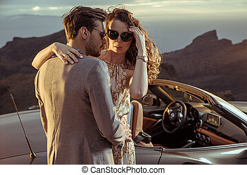 Elegant lovers posing next to the convertible