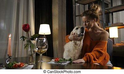 Elegant loving woman cuddling her pet dog indoors - Elegant...