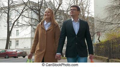 Elegant man and woman walking after shopping