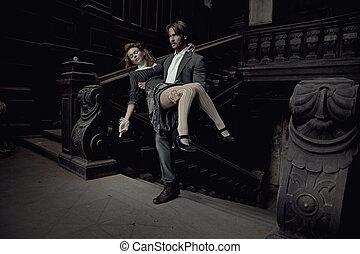 Elegant man carrying a beautiful brunette