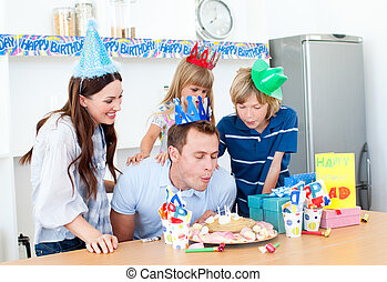 Elegant man celebrating his birthday with his wife and his children in the kitchen