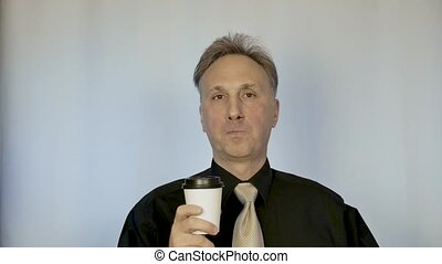 Elegant man drinking coffee. he is in a good mood. portrait