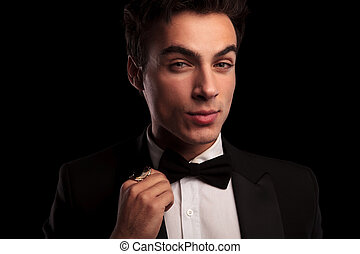elegant man fixing his bowtie and wearing a big ring
