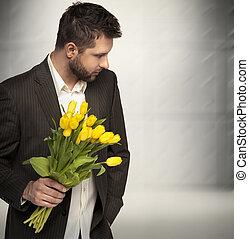 Elegant man holding flowers