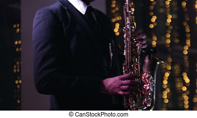 Elegant man in a black smoking jacket is playing on a saxophone in a restaurant. Artist is playing music on his instrument, stage decorated with yellow lights on a background.