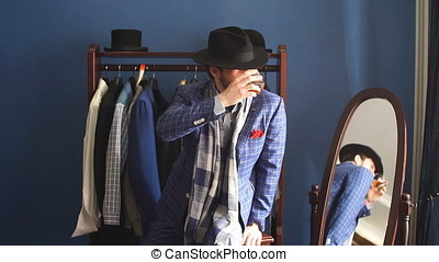Elegant man in fashion suit and hat posing at atelier with beverage.
