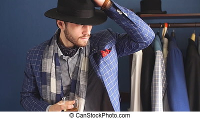 Elegant man in fashion suit and hat posing at atelier with beverage
