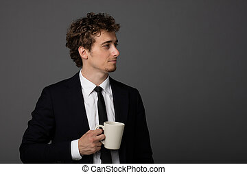 elegant man in suit with a cup on gray background