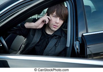 Elegant man talking over cellphone in his car
